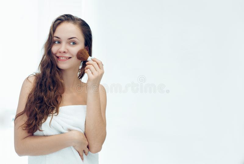 Beautiful girl with cosmetic powder brush for make up. Makeup. Make-up applying  for perfect skin.  royalty free stock image