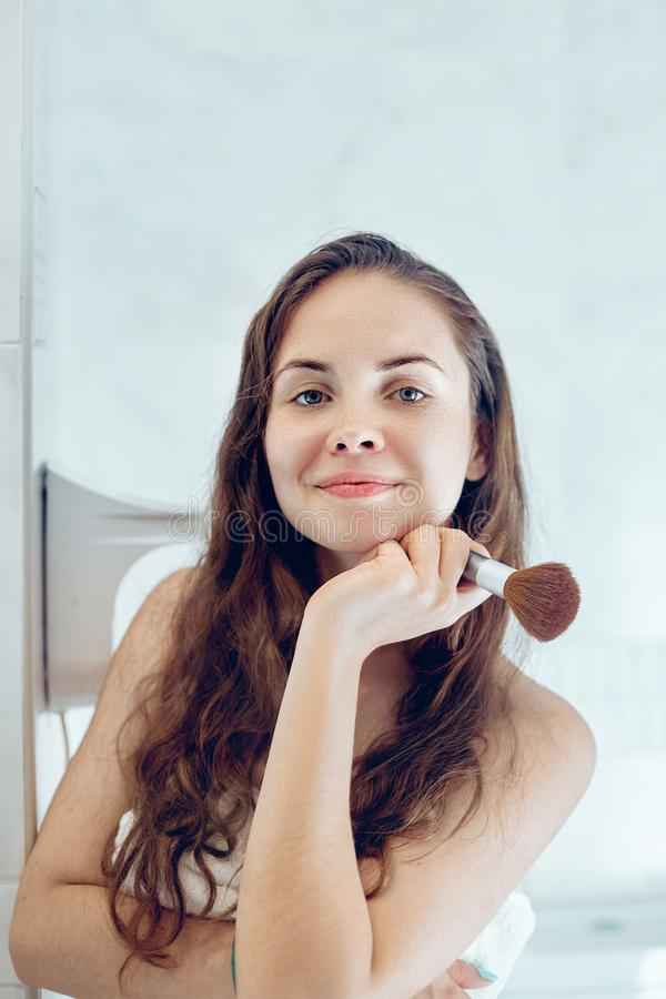 Beautiful girl with cosmetic powder brush for make up. Makeup. Make-up applying  for perfect skin. Beautiful girl with cosmetic powder brush for make up. Makeup stock photography