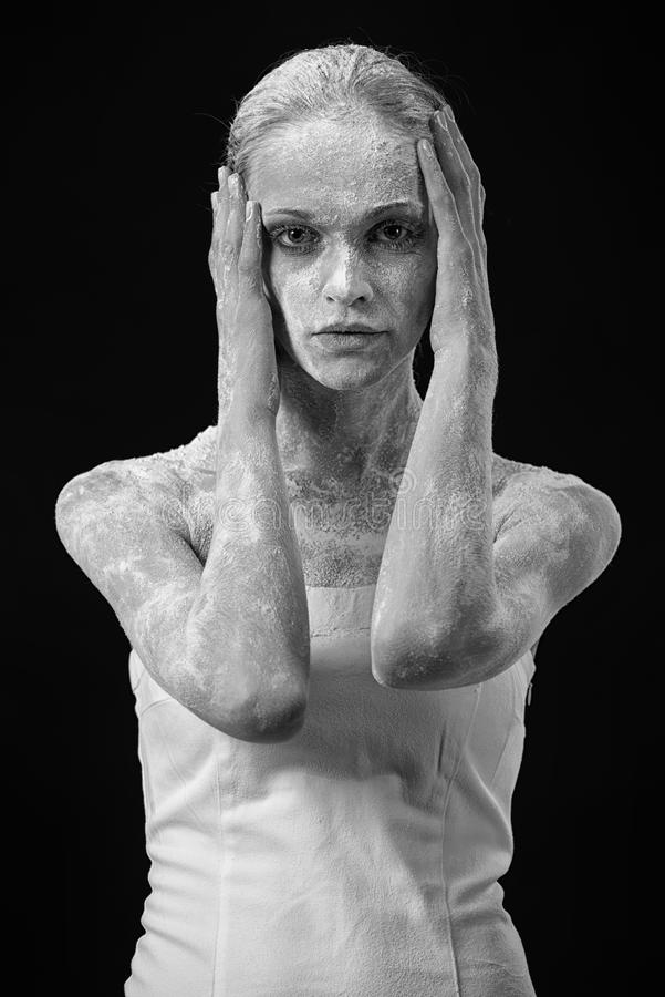 Beautiful girl covered in white dust. Art portrait of a Beautiful girl covered in white dust over black background royalty free stock images
