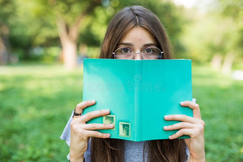 Beautiful girl covering her face with book. Education and people concept. stock photo