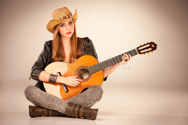 The beautiful girl in a cowboy's hat and acoustic guitar. royalty free stock image