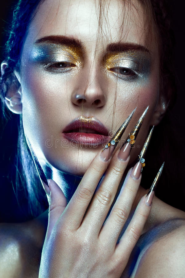 Beautiful girl with creative golden and silver glitter make-up, long nails art. beauty face. stock photography