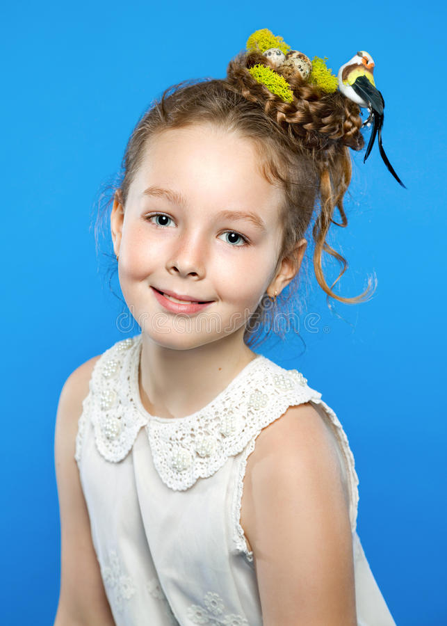 Beautiful girl with creative hairstyle. Nest, eggs, bird. Blue background royalty free stock photos