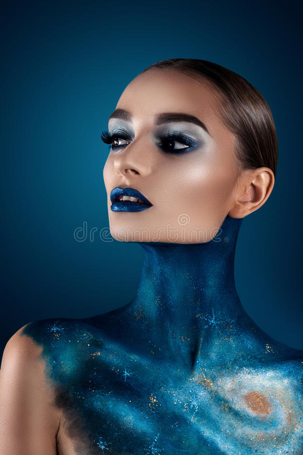 Beautiful girl with creative make-up . Bright colors blue lips. Conceptual art the cosmos, the universe. On a dark blue background royalty free stock photos