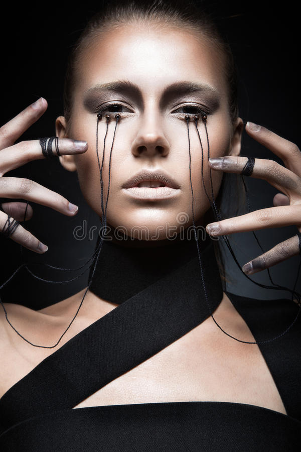 Beautiful girl with creative make-up in Gothic. Style and the threads of eyes. Art beauty face. Picture taken in the studio on a black background stock photography