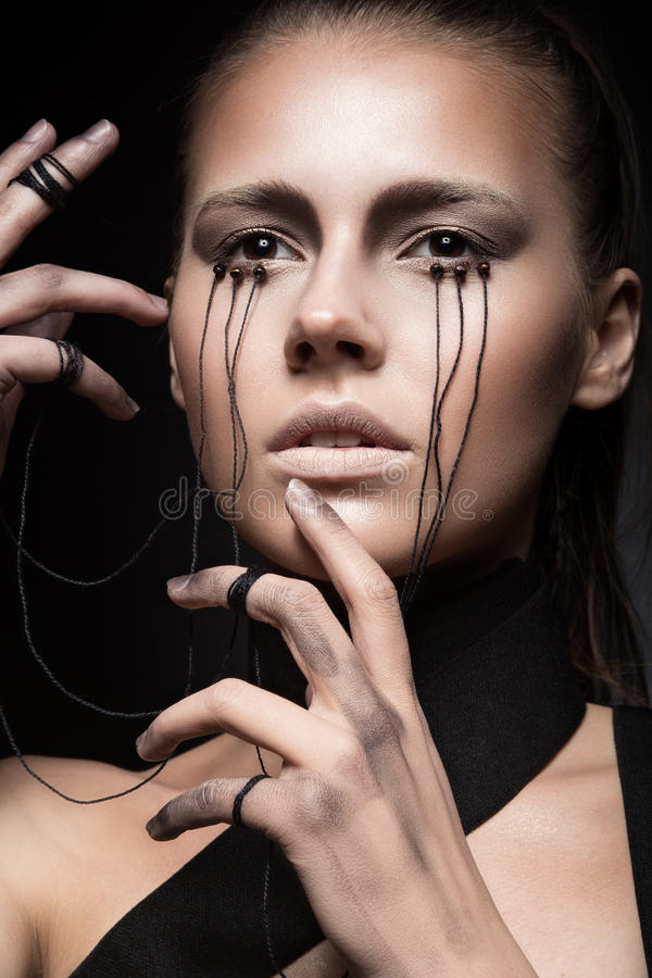 Beautiful girl with creative make-up in Gothic style and the threads of eyes. Art beauty face. Picture taken in the studio on a black background royalty free stock photos
