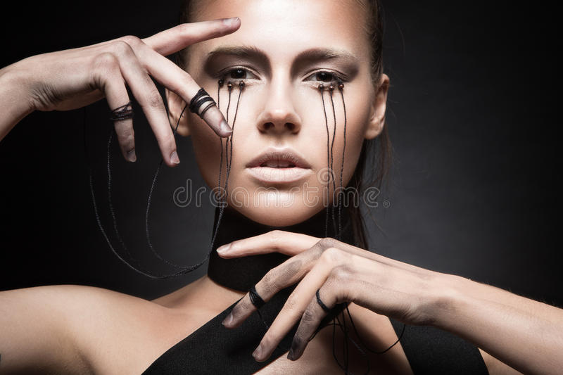 Beautiful girl with creative make-up in Gothic style and the threads of eyes. Art beauty face. Picture taken in the studio on a black background royalty free stock images