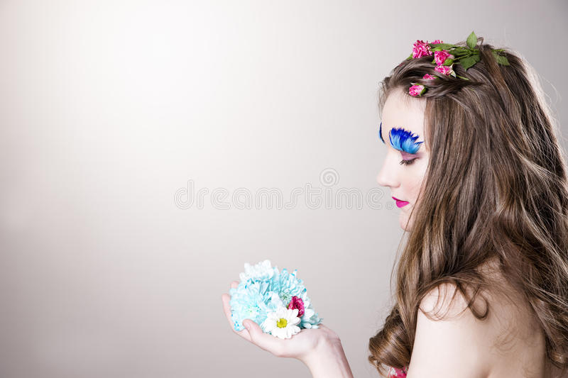 Beautiful girl with creative make-up and hairstyle with flowers. Portrait of a beautiful young woman on a gray background. Girl with creative make-up and royalty free stock image