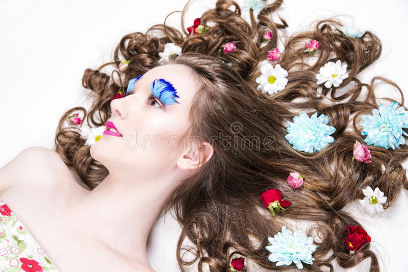 Beautiful girl with creative make-up and hairstyle with flowers. Portrait of a beautiful young woman on a white background. Girl with creative make-up and stock image