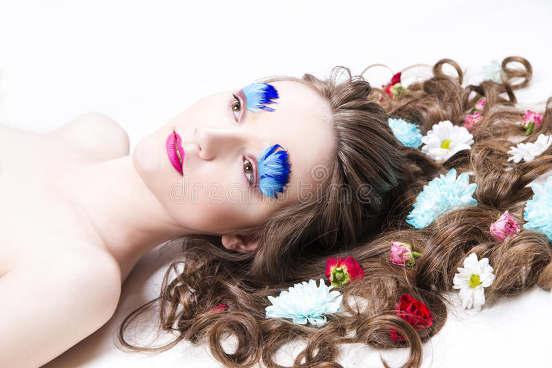 Beautiful girl with creative make-up and hairstyle with flowers. Portrait of a beautiful young woman on a white background. Girl with creative make-up and royalty free stock images