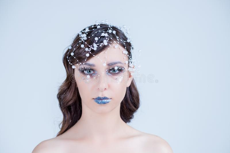 Beautiful girl with creative make-up for the new year. Winter portrait. Bright colors, blue lips, elegant design hair stock image