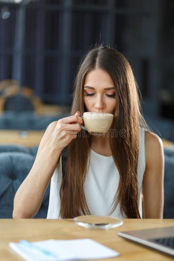 A beautiful girl and a cup of cappuccino stock photos