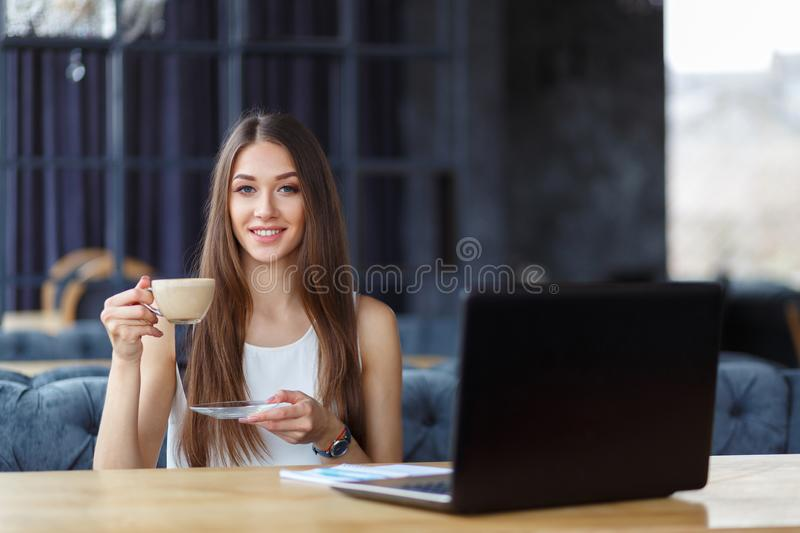 A beautiful girl and a cup of cappuccino stock image