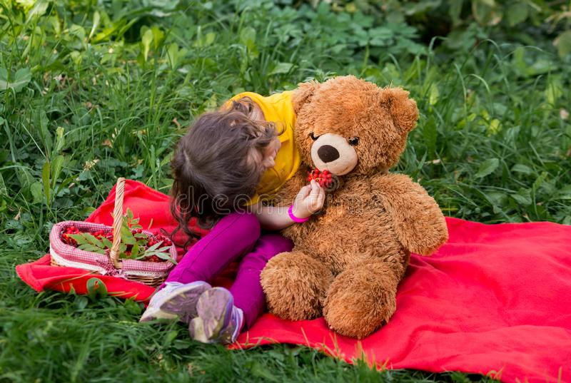 Beautiful girl with curls and bangs in a yellow jacket hugs her friend - a teddy bear. friendship baby and toys. picnic in the royalty free stock photos