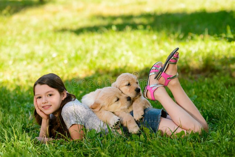Beautiful girl and cute dogs. Owner and her golden retriever puppies are resting in the countryside field. Summertime memories royalty free stock photos