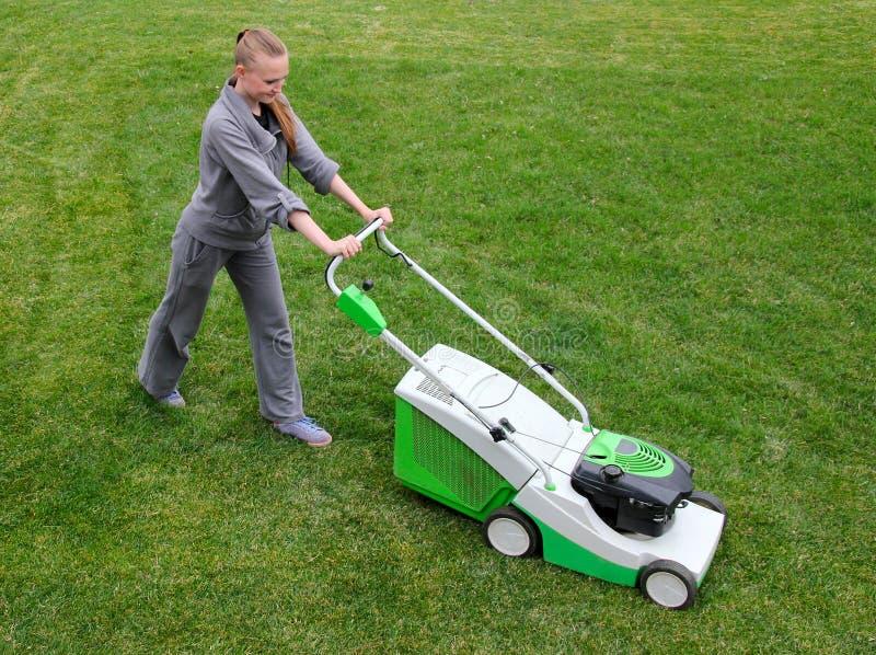 Beautiful girl cuts the lawn stock photo