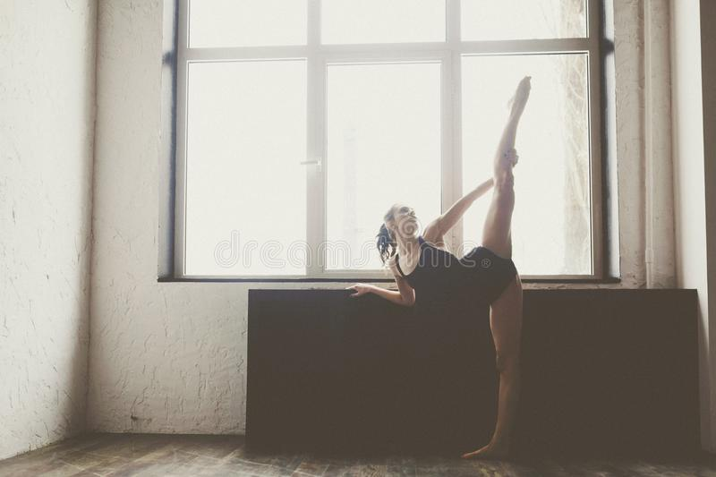 Beautiful girl dancer in black clothes,in beautiful pose,raised straight leg over her head,Fuete against window background. Silhou stock images