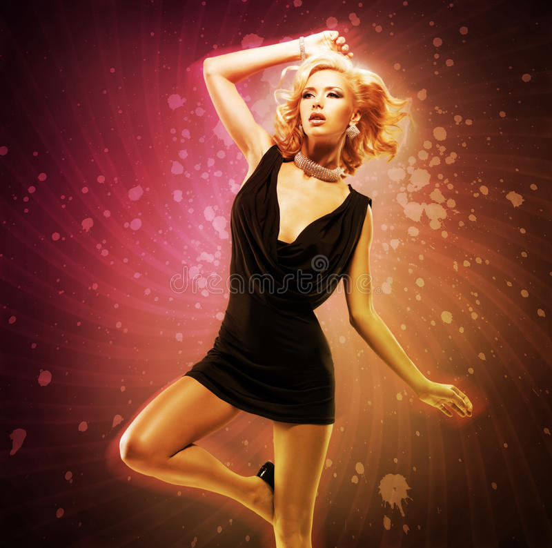 Beautiful girl dancer in black dress in creative pose over art. Bright color background royalty free stock image