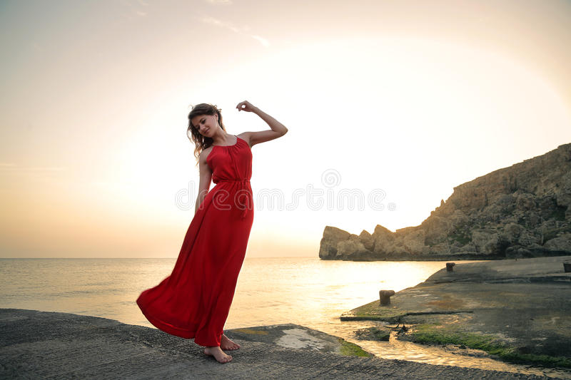 Beautiful girl dancing on a pier with a red dress royalty free stock photos