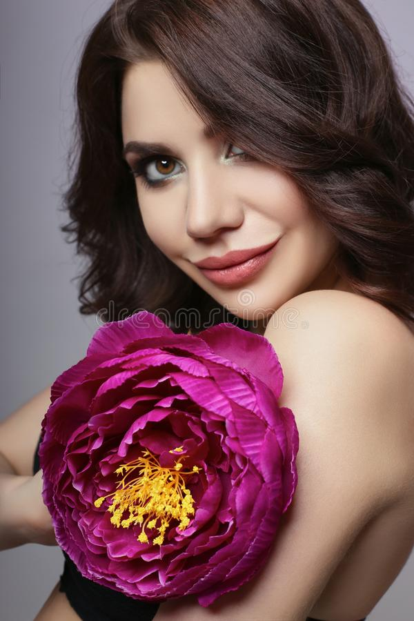 Beautiful girl with dark hair and big flower near face. Large pu. Rple peony flower near woman`s face. Beautiful makeup and pure natural skin, skin care and stock photography