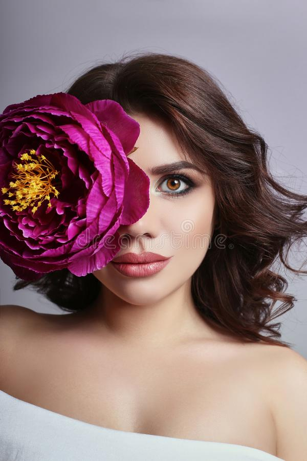 Beautiful girl with dark hair and big flower near face. Large pu. Rple peony flower near woman`s face. Beautiful makeup and pure natural skin, skin care and stock image