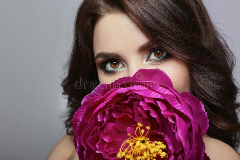 Beautiful girl with dark hair and big flower near face. Large pu. Rple peony flower near woman`s face. Beautiful makeup and pure natural skin, skin care and royalty free stock photography