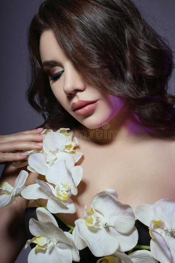 Beautiful girl with dark hair and big flower near face. White li. Ly flower near woman`s face. Beautiful makeup and pure natural skin, skin care and professional royalty free stock image