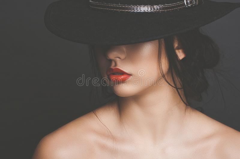 Beautiful girl with dark hair in a black hat royalty free stock photography