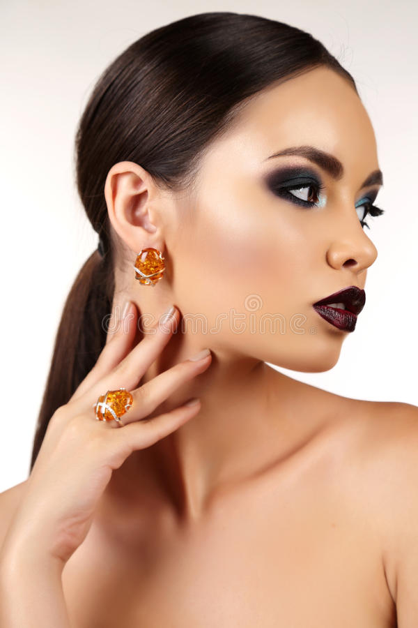 Beautiful girl with dark hair with bright extravagant makeup and bijou. Fashion studio portrait of beautiful girl with dark hair with bright extravagant makeup royalty free stock image
