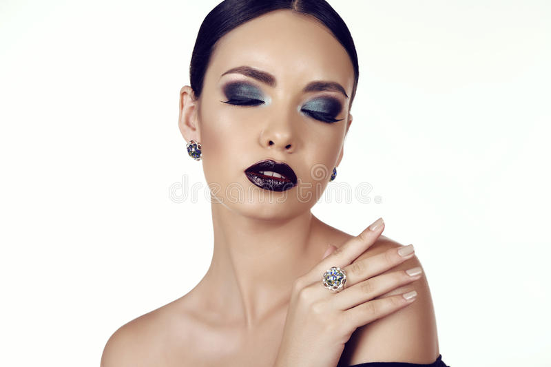 Beautiful girl with dark hair with bright extravagant makeup and bijou. Fashion studio portrait of beautiful girl with dark hair with bright extravagant makeup stock photography