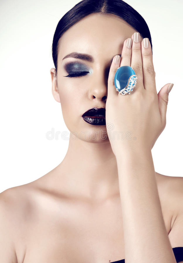 Beautiful girl with dark hair with bright extravagant makeup and bijou. Fashion studio portrait of beautiful girl with dark hair with bright extravagant makeup royalty free stock photography