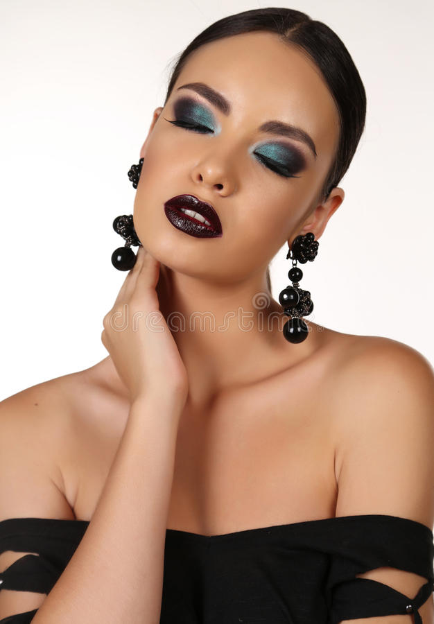 Beautiful girl with dark hair with bright extravagant makeup and bijou. Fashion studio portrait of beautiful girl with dark hair with bright extravagant makeup royalty free stock photo