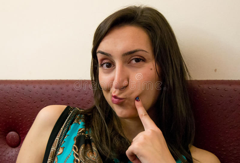Beautiful girl with dark hair and dark eyes making a funny face. Looking straight forward royalty free stock photography