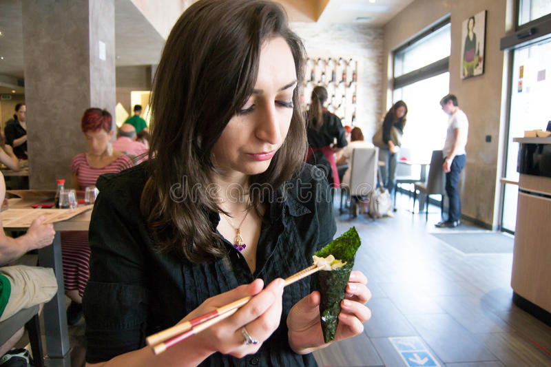Beautiful girl with dark hair, dressed in black is holding chopsticks and temaki sushi. In a restaurant royalty free stock image