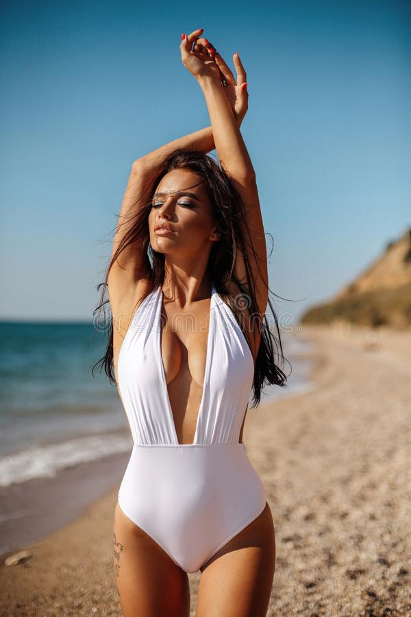 Beautiful girl with dark hair in elegant swimming suit relaxing on the summer beach stock photo