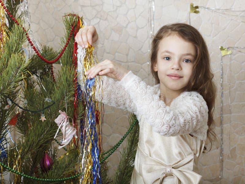 Beautiful girl decorates the Christmas tree. stock image