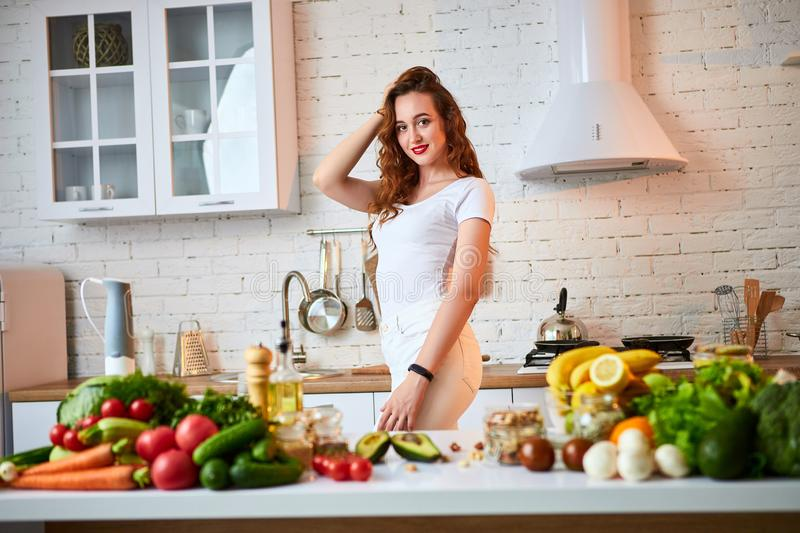 Beautiful girl demonstrates her perfect figure against the background of healthy food in the kitchen.  Health, Beauty, Diet royalty free stock photo
