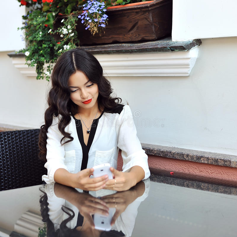 Beautiful girl dialing number on a mobile phone - outdoor stock photo