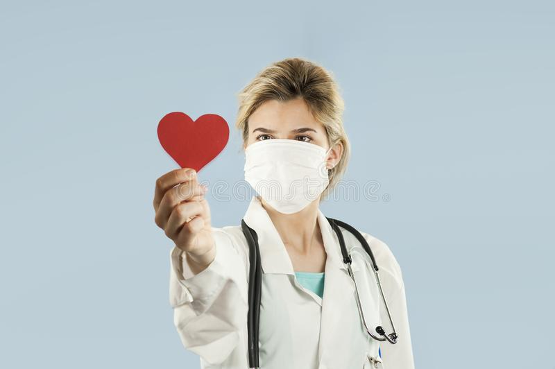 Beautiful girl doctor with a red heart in her hands on a blue isolated background.Concept of love stock photo