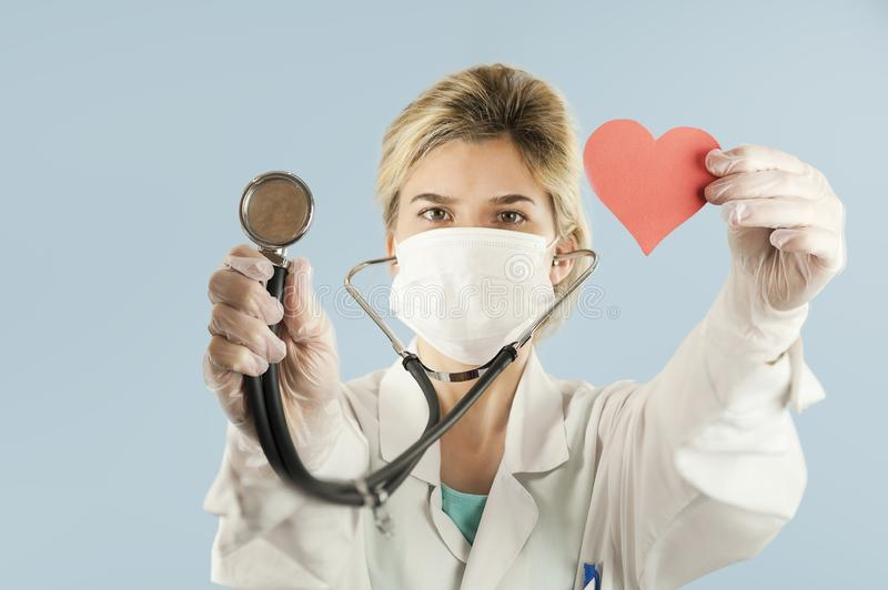 Beautiful girl doctor with a red heart in her hands on a blue isolated background.Concept of love royalty free stock photo