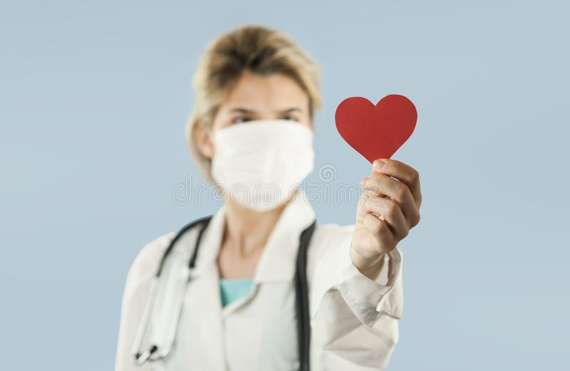 Beautiful girl doctor with a red heart in her hands on a blue isolated background.Concept of love royalty free stock images