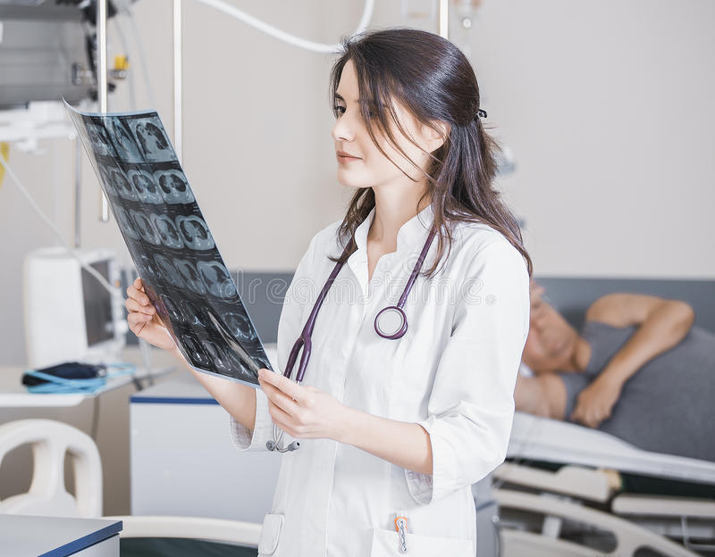 Beautiful girl doctor in a white coat examines X-ray photo of the patient to identify the problem. Professional conversation, cons. Ultation of doctors. The work royalty free stock photo