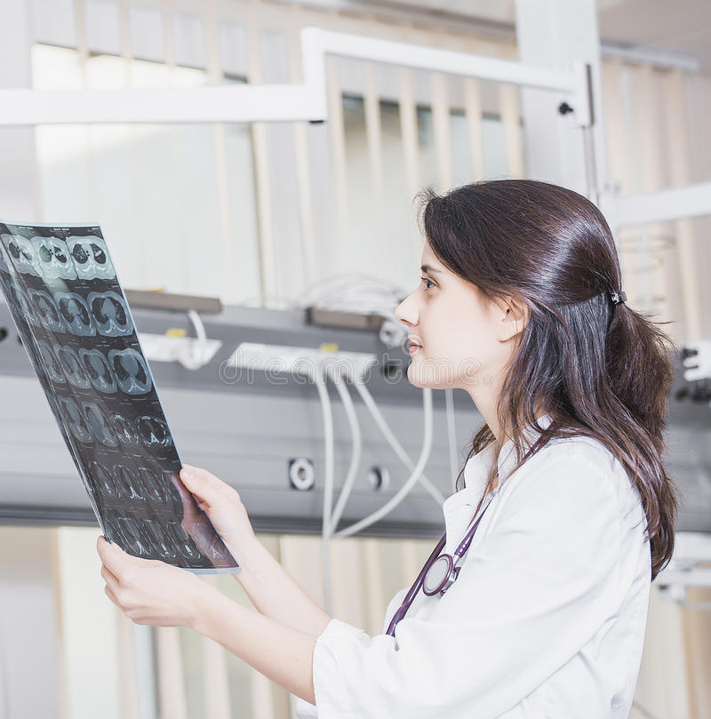 Beautiful girl doctor in a white coat examines X-ray photo of the patient to identify the problem. Professional conversation, cons. Ultation of doctors. The work stock photo