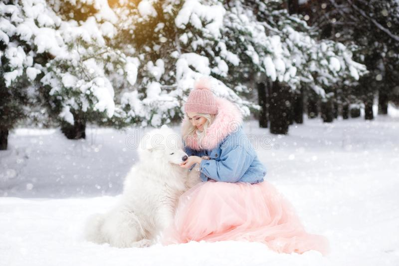 Beautiful girl with a dog on a walk in the winter forest. beautiful girl and her pet.  stock photography