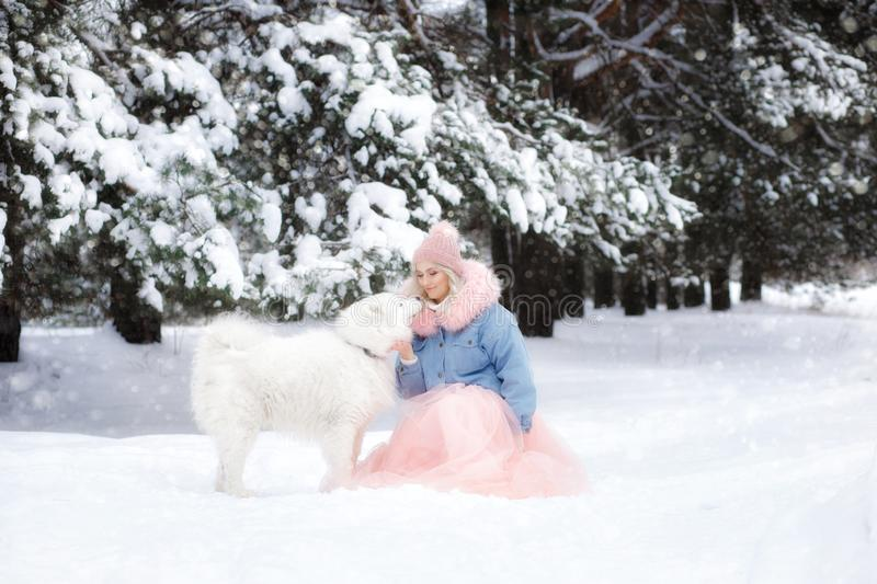 Beautiful girl with a dog on a walk in the winter forest. beautiful girl and her pet.  stock photos
