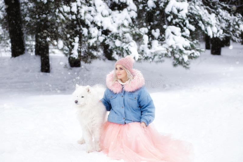 Beautiful girl with a dog on a walk in the winter forest. beautiful girl and her pet.  royalty free stock photography