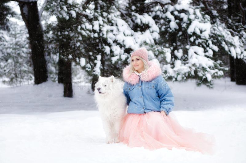 Beautiful girl with a dog on a walk in the winter forest. beautiful girl and her pet.  stock images