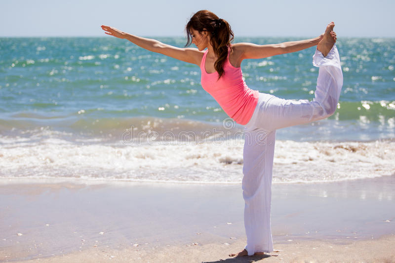 Beautiful girl doing some yoga. Gorgeous Latin girl maintaining balance for a yoga pose at the beach royalty free stock image