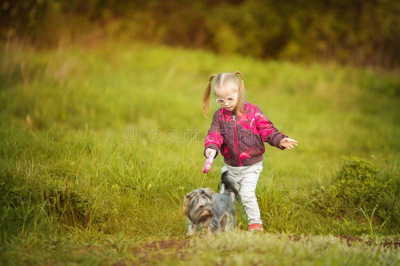 Beautiful girl with Down syndrome hugs puppy royalty free stock images