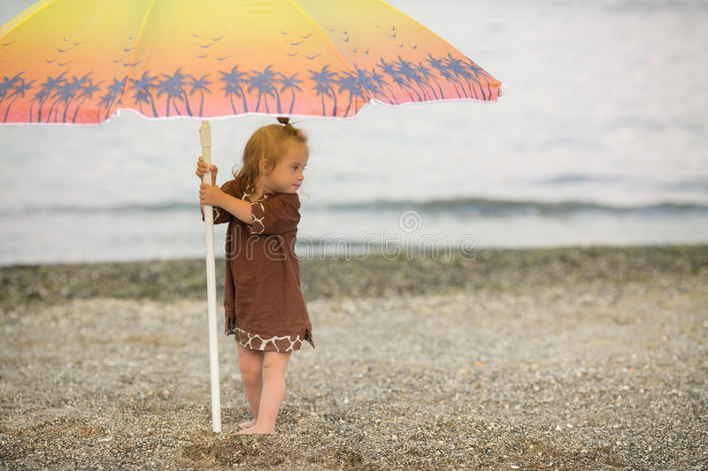 Beautiful girl with Down syndrome standing under an umbrella on the beach royalty free stock photo